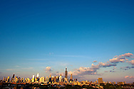 A few summer afternoon puffy clouds roll over the Chicago skyline, as seen from the west side of the city.