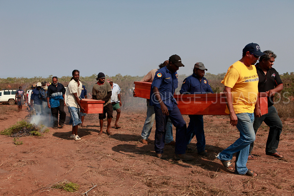 Men carrying three coffins into the sand dunes. The repatriation of skeletal remains are now being collected by scientists and returned to their ancestral homeland.  In the Bidyadanga community the remains of 17 Kimberley Aboriginal people have been returned home more than a century after they were taken and put on display in museums around Australia.  Bidyadanga community in WA