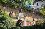 Statues in park on Paseo la Princesa with colorful houses in background; Old San Juan, Puerto Rico.