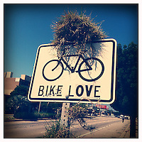 """Grass grows on a Bike Lane sign modified to read """"Bike Love"""" on Venice Blvd in Los Angeles, California on May 14, 2012."""