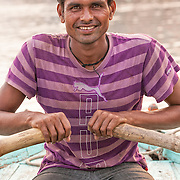 A young man works as a boatman transporting tourists up and down the Ganges River in the Old City section of Varanasi India