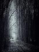 Man walking on railway tracks towards the light - manipulated monochrome photograph.