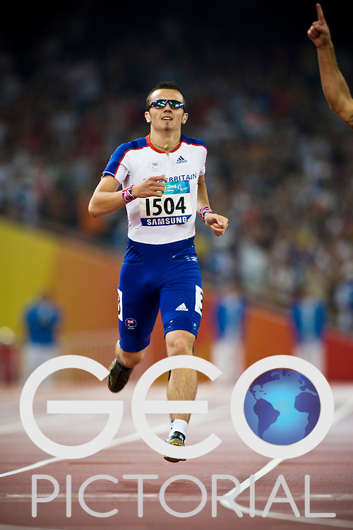 """Ian Jones of Great Britain runs across the finish line in the men's T44 400m final to win the Bronze medal on Day 8 of the 2008 Beijing 2008 Paralympic Games at the National """"Bird's Nest"""" Stadium in Beijing, China on the 16th September 2008;"""