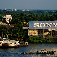 Vietnam, Ho Chi Minh City..Globalisation. Trade. Imports. Advertising for Sony, with Konica ad on ferry, standing over the jungle facing on to the Saigon River. ..©Mark Henley