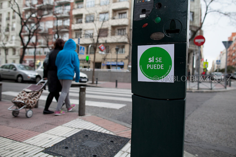 Neighbors walk in the street after Anti-eviction activists took part in a 'escrache' outside the house of Popular Party Deputy Mari Luz Prieto, on April 4, 2013 in Madrid, Spain. Sticker reads 'Yes we can'. The Mortgage Holders Platform (PAH) and other anti evictions organizations are organizing 'escraches' for several weeks under the slogan 'There are lifes at risk' to claim the vote for a Popular Legislative Initiative (ILP) to stop evictions, regulate dation in payment and social rent outside Popular Party deputies' houses and offices..'Escraches' are form of peaceful public protest that was used in Argentine in 1995 to point to pardoned genocides of Argentenia's Dictatorship within their neighborhoods.