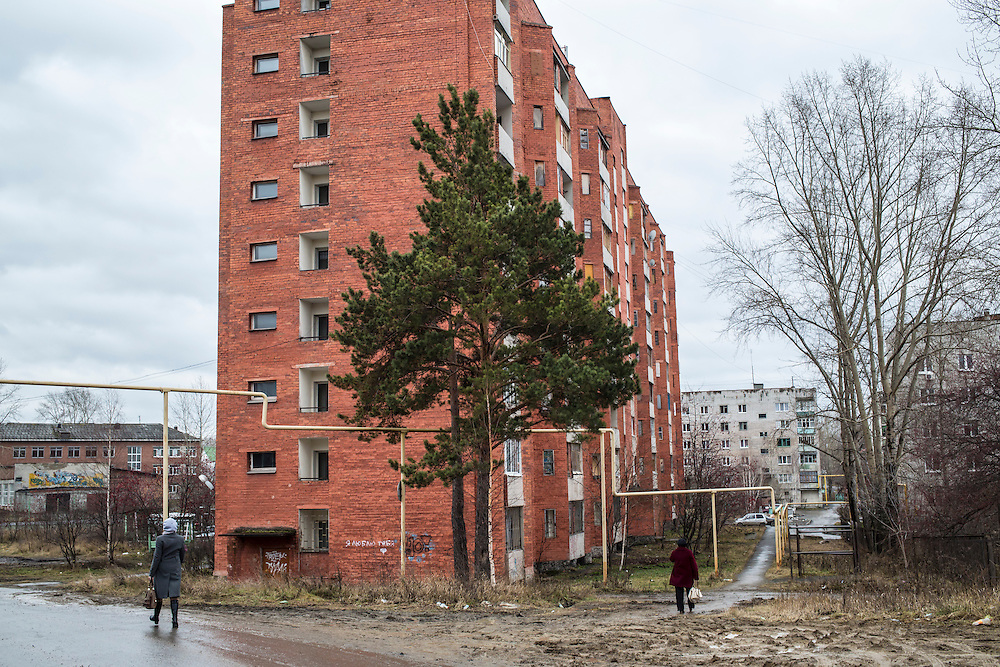 Women walk past an apartment building on Monday, November 11, 2013 in Asbest, Russia.