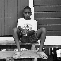 Young boy sitting on the front porch of his green painted home on the island of Bastimento, Bocas del Toro, Panama