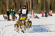 Musher Melissa Owens competing in the 44th Iditarod Trail Sled Dog Race on Long Lake after leaving the restart on Willow Lake in Southcentral Alaska.  Afternoon. Winter.