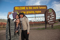 """College student friends:  Enka, Lores and Lizbeth snap a """"selfie"""" near Calistoga while in front of the single most photographed sign in the Northern California,  enka@gmail.com"""
