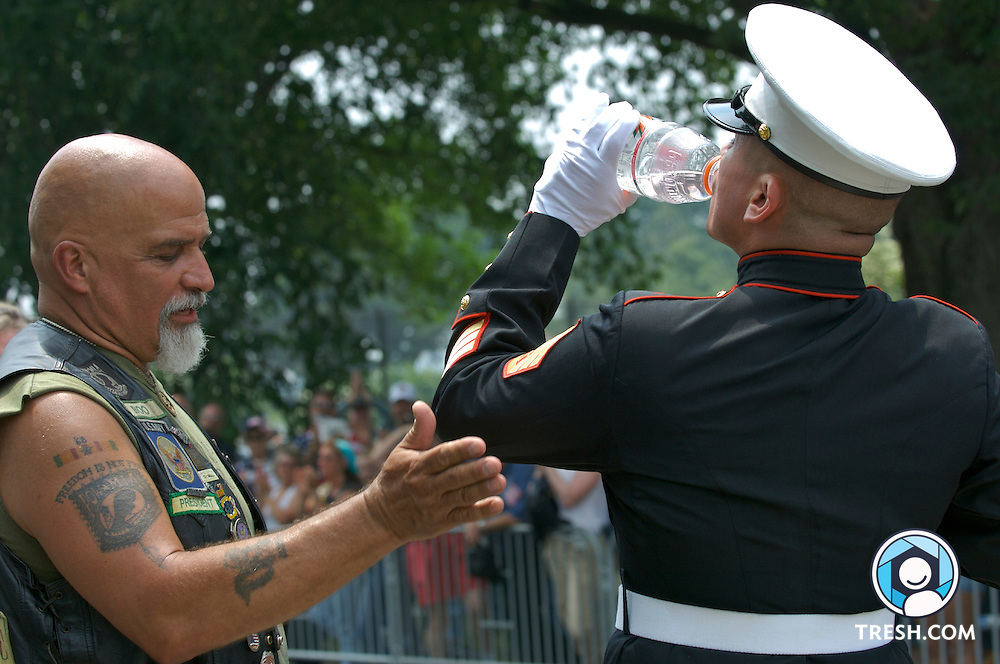 A veteran provides water to U.S. Marine Staff Sergeant Tim Chambers, during a break in the motorcycle procession. To honor fallen service members, Chambers stood at attention for hours on the meridian facing the Lincoln Memorial saluting between columns of riders during Rolling Thunder XX, Sunday, May 27, 2007, Washington, D.C.