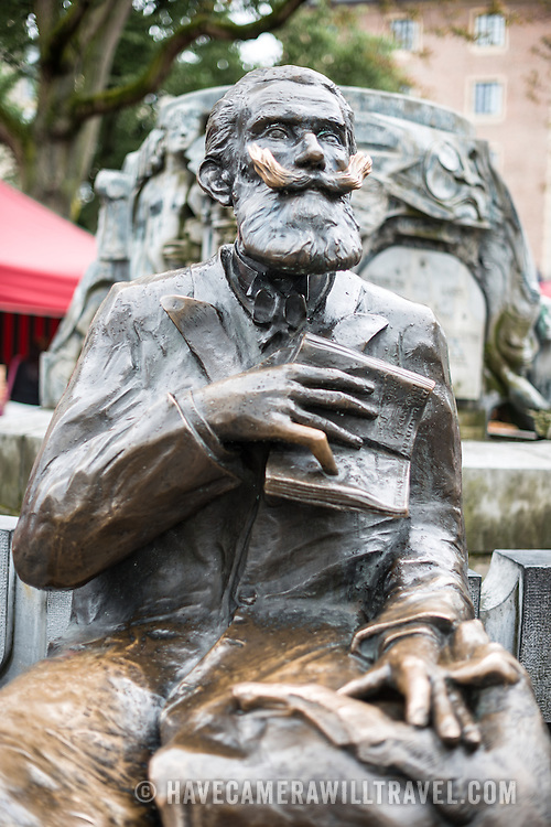 A statue of Karel Buls (Charles Buls), a former mayor of the City of Brussels (from 1881 to 1899). The statue sits in Grasmarkt/Rue du Marché aux Herbes-Agora Square in the city's Lower Town.