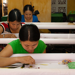 HOI AN, VIETNAM - AUGUST 30: Three unidentified textile workers in a small factory in Hoi An, August 30, 2010. Textiles trade earned around 17mln USD in 2006 (Dept of Planning&Investment)