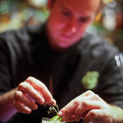 "SHOT 10/8/09 10:58:49 AM - TAG restaurant on Larimer Square in downtown Denver, Co. The restaurant operated by chef/owner Troy Guard features what they term ""continental social food"" and features influences from numerous continents. Mixologist Jared Boller puts the finishing touches on the Business Thyme ($10) at the bar in TAG. The drink consists of 42 below passion fruit vodka, dimmi liqueur de milano, kiwi, thyme, orange flower water, and lime served over ice in a collins glass (2nd place cocktail in the 42 below regional cocktail kickoff competition).  (Photo by Marc Piscotty / © 2009)"