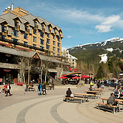 People enjoy the Whistler Village in sidewalk cafes and restaurants on a sunny day in the spring.  Whistler BC, Canada