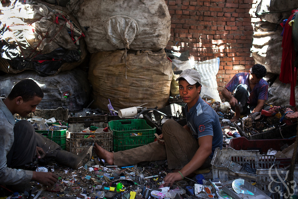 """Egyptian garbage collectors sort garbage to recycle in the Manshiyet Nasr neighborhood of Cairo, Egypt June 5, 2009. The majority coptic christian garbage collectors, known as """"zabbaleen"""", (""""garbage people"""" in arabic), recently have had to adapt to a new way of working after the Egyptian government confiscated and killed all the pigs in their area. Pigs are important to the zabbaleen, since the pigs are used to dispose of all the organic bits of trash collected."""