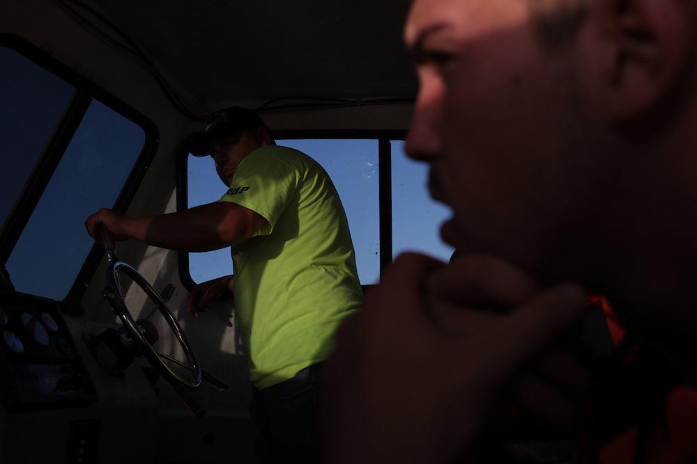 Eric Melerine and his brother Allen Labat pulling in hard boom around Pelican Island, LA August 30, 2010.