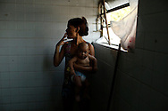 """A woman holding her baby smokes a cigarette as she waits for a washing machine, before doing laundry inside the bathroom at the Nova Tuffy slum, in an abandoned factory in Rio de Janeiro, October 17, 2014. Since seven months ago, 1,800 families have been living inside the factory, which they occupied in March, with poor sanitation services and the fear of eviction. The occupants of the factory say they are not included in the housing program """"Minha Casa, Minha Vida"""" (My House, My Life), and they would like to be included by the Brazilian government. The housing program is one of several government initiatives aimed at reducing poverty and social inequality that President Dilma Rousseff has held up as achievements of her administration as she campaigns for re-election. Photo/Pilar Olivares"""