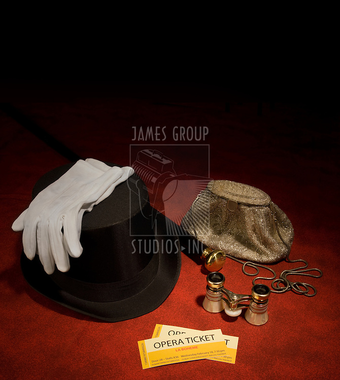 Two opera tickets propped with a top hat, cane, white gloves, a purse and opera glassees
