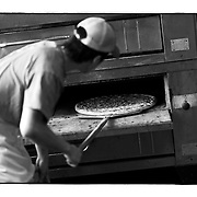 """SHOT 8/10/09 5:43:08 PM - A pizza chef checks on a pizza in the oven at Fat Sully's New York Style PIzza on Colfax Avenue in Denver, Co. Colfax Avenue is the main street that runs east and west through the Denver-Aurora metropolitan area in Colorado. As U.S. Highway 40, it was one of two principal highways serving Denver before the Interstate Highway System was constructed. In the local street system, it lies 15 blocks north of the zero point (Ellsworth Avenue, one block south of 1st Avenue). For that reason it would normally be known as """"15th Avenue"""" but the street was named for the 19th-century politician Schuyler Colfax. On the east it passes through the city of Aurora, then Denver, and on the west, through Lakewood and the southern part of Golden. Colloquially, the arterial is referred to simply as """"Colfax"""", a name that has become associated with prostitution, crime, and a dense concentration of liquor stores and inexpensive bars. Playboy magazine once called Colfax """"the longest, wickedest street in America."""" However, such activities are actually isolated to short stretches of the 26-mile (42 km) length of the street. Periodically, Colfax undergoes redevelopment by the municipalities along its course that bring in new housing, trendy businesses and restaurants. Some say that these new developments detract from the character of Colfax, while others worry that they cause gentrification and bring increased traffic to the area. (Photo by Marc Piscotty / © 2009)"""