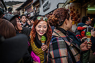 A Chinese-speaking tourist happily carts away a green tea ice cream cone, a Japanese speciality, through the crowd on the main approach to Kiyomizu Temple.  Tourist buses, full of tourists from the Chinese mainland, deliver tourist groups to this popular street, lined with gift shops.  Kyoto, Japan.  <br /> <br /> Japan has relaxed tourist visa restrictions, combined with a weak Japanese yen, leading to a tourism boom mostly from China, but also from Southeast Asia.  Crowds now clog many of Kyoto's tourist sites on the one hand but merchants business has not been so good in decades.  In fact, the Japan Times newspaper reports, Japan logged a travel account surplus in 2014 for the first time in 55 years, where &yen; 209.9 billion more yen was brought into Japan by foreign tourists, than Japanese tourists spent abroad.