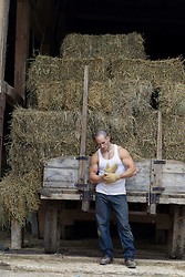 farm worker putting on work gloves while standing next to hay bales on a truck