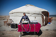 "A man sets up DJ booth in front of traditional portalble wood-framed house ""yurt."""