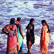 Five women in saris walking at the seashore. Taken in 1979 with a 35 mm Nikon FM.