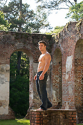 Shirtless rugged man standing on a platform in  abandoned church ruins