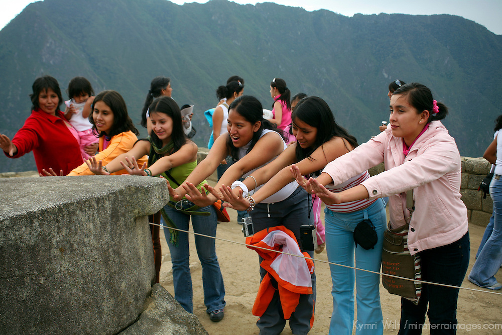 South America, Peru. Women with arms outstretched to feel the energy of the stone at Machu PIcchu, a UNESCO World Heritage Site.