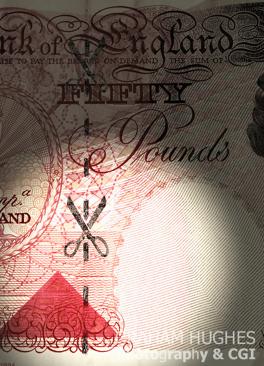 £50 pound British bank note with scissors cutting along dotted security line.