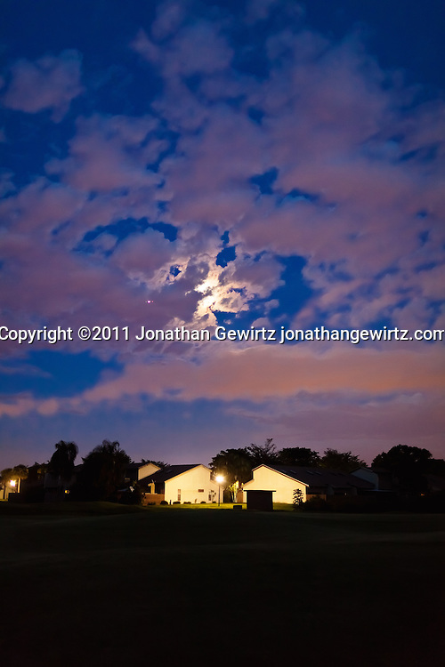 The full moon is hidden by a partly cloudy sky over homes on a Davie, Florida golf course. WATERMARKS WILL NOT APPEAR ON PRINTS OR LICENSED IMAGES.