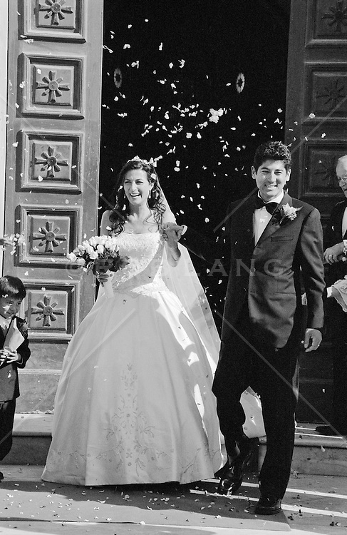 Bride and Groom leaving the church with flower petals tossed at them