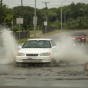 NORFOLK, VA - JULY 4: A driver navigates a flooded intersection at 4th View and West Ocean View Avenue in Willoughby on Friday, July 4th, 2014 in Norfolk, Va. (Photo by Jay Westcott/For The Virginian-Pilot)