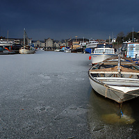 Boats trapped in ice as the Exeter canal basin is covered in a layer of ice.
