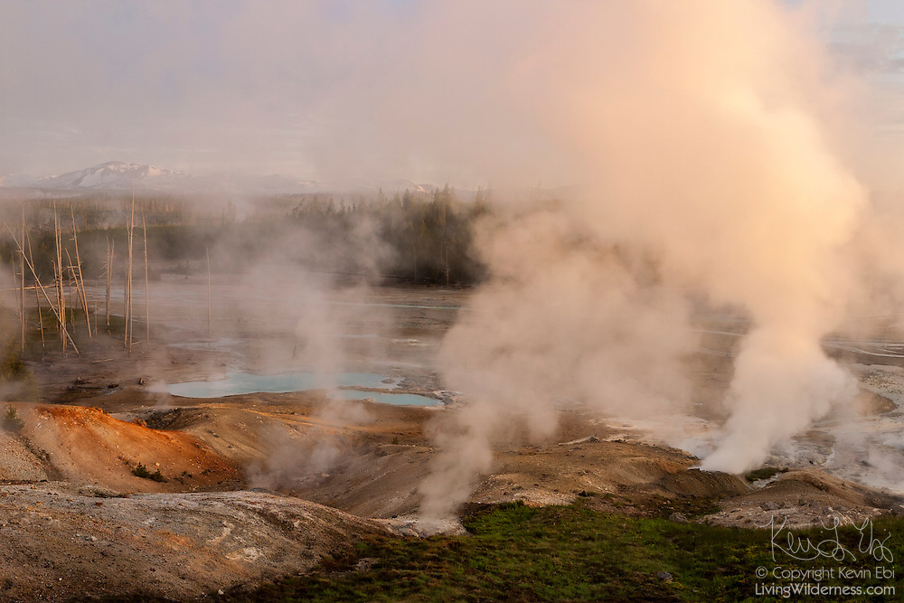 Steam from vents, or fumaroles, in the Norris Basin of Yellowstone National Park, Wyoming, rises at sunrise, partially framing the Gallatin Mountains. In the foreground at left is Ledge Geyser, which once was the second largest geyser in the area, capable of shooting water 125 feet (38 meters) into the air. It has been largely inactive since 1995.