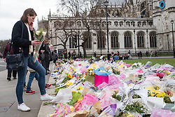 © Licensed to London News Pictures. 29/03/2017. London, UK. A woman lays flowers in Parliament Square shortly before a minute's silence held at 14:40, exactly one week after Khalid Masood began a terrorist attack on Westminster. Photo credit: Rob Pinney/LNP