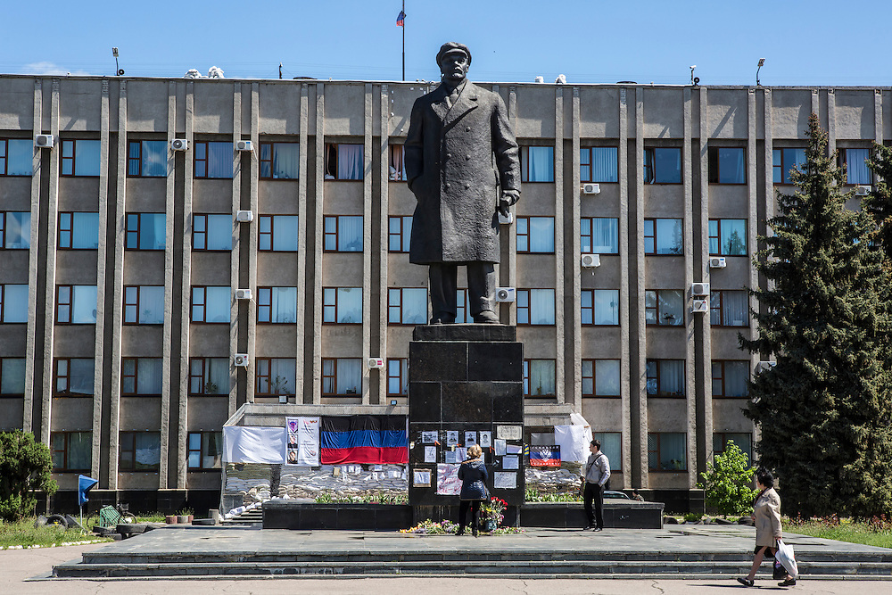 SLOVYANSK, UKRAINE - MAY 6:  People pass through central Lenin Square and the occupied city administration building, where the local resistance is headquartered, on May 6, 2014 in Slovyansk, Ukraine. Tensions in Eastern Ukraine are high after pro-Russian activists seized control of at least ten cities and ahead of the Victory Day holiday and a planned referendum on greater autonomy for the region. (Photo by Brendan Hoffman/Getty Images) *** Local Caption ***