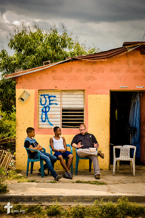 The Rev. Joel Fritsche, LCMS career missionary to the Dominican Republic, visits with two young church members at a home near his parish of Amigos de Cristo Iglesia Luterana in Las Americas (Friends of Christ Lutheran Church in the Americas) on Saturday, March 18, 2017, in Santo Domingo. LCMS Communications/Erik M. Lunsford