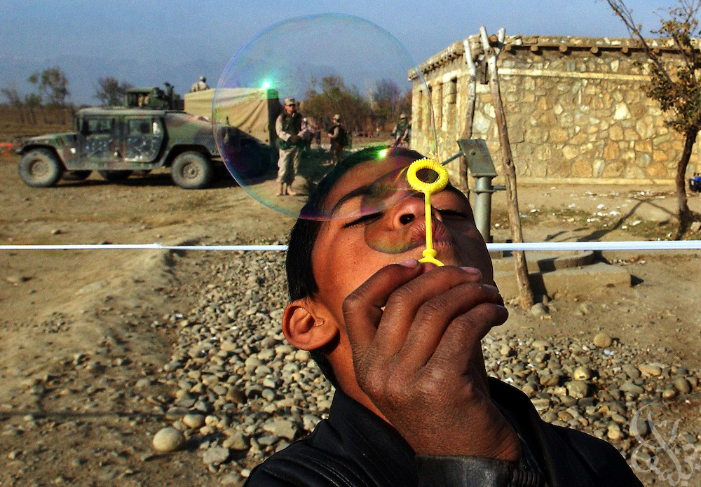 An Afghan boy blows bubbles given to him by US Army troops (seen in background) during a December 03, 2002 civil humanitarian mission in the village of Tadokhile in central Afghanistan. The mission provided more than a hundred Afghan men, women and children from the village with free medical care and basic dentistry as part of the ongoing Operation Enduring Freedom.  In addition to the free health clinic, soldiers also distributed school supplies and toys to local Afghan children. US military leaders have recently indicated a shift away from combat operations in the war in Afghanistan while increasing the emphasis on civil humanitarian efforts to rebuild the country and provide stability for the new government.