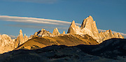 """A golden sunrise spotlights Mount Fitz Roy (3405 meters or 11,170 feet), which rises abruptly on the border between Argentina and Chile in the Southern Patagonian Ice Field in the Andes mountains, near El Chaltén village, in Los Glaciares National Park, Argentina, South America. In 1877, explorer Perito Moreno named """"Cerro Fitz Roy"""" for Robert FitzRoy (no space before the capital R) who, as captain of the HMS Beagle, had travelled up the Santa Cruz River in 1834 and charted much of the Patagonian coast. First climbed in 1952 by French alpinists Lionel Terray and Guido Magnone, Mount Fitz Roy has very fickle weather and is one of the world's most challenging technical ascents. It is also called Cerro Chaltén, Cerro Fitz Roy, and Monte Fitz Roy (all with a space before the R). Chaltén comes from a Tehuelche (Aonikenk) word meaning """"smoking mountain"""" (explained by frequent orographic clouds). Cerro is a Spanish word meaning hill. El Chaltén village was built in 1985 by Argentina to help secure the disputed border with Chile, and now tourism supports it, 220 km north of the larger town of El Calafate. The foot of South America is known as Patagonia, a name derived from coastal giants, Patagão or Patagoni, who were reported by Magellan's 1520s voyage circumnavigating the world and were actually Tehuelche native people who averaged 25 cm (or 10 inches) taller than the Spaniards. Mount Fitz Roy is the basis for the Patagonia company's clothing logo, after Yvon Chouinard's ascent and subsequent film in 1968.  Panorama stitched from 3 overlapping photos. Published in """"Light Travel: Photography on the Go"""" by Tom Dempsey 2009, 2010."""