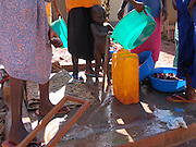 Gulu, Uganda, 2004. Women, mostly teenage mothers, wash children and clothes at GUSCO, a reception centre for Lord's Resistance Army departees.