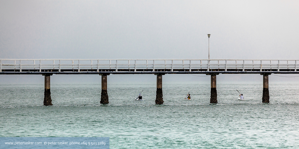 Three kayakers paddling under Orakei Wharf, Okahu Bay, Auckland, New Zealand.