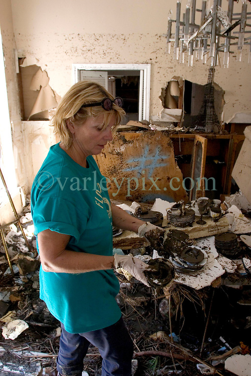 08 Sept 2005.  New Orleans, Louisiana. Hurricane Katrina aftermath. <br /> Venetian Isles in East New Orleans, where the tidal surge washed over the land and devastated homes and property. Peggy Lala struggles to save personal effects from her mud filled flood ravaged home.<br /> Photo; &copy;Charlie Varley/varleypix.com