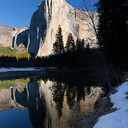 El Capitan, a prominent granite monolith in Yosemite National Park, California, reflects in the Merced River at sunrise. The summit of El Capitan is at an elevation of 7,573 feet (2,308 meters); it extends about 3,000 feet from the Yosemite Valley floor. The change of seasons from winter to spring is visible in the melting snow on the river banks.