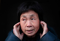 Chinese villager Xie Pingying of Xiangnan Village covers her ears from the noise pollution caused by a chemical plant just outside their village in Zekou Town, Qianjiang City of Hubei Province, China 14 January 2013. Xie says the constant noise from the chemical plant caused her immense stress and also suffers from heart, throat and eye problems due to the pollution. While the heavy smog in Beijing and much of northern China in recent days have caused alarm among residents and renewed scrutiny on the pollution woes of the country, villagers in a small town of Hubei Province have been grappling with severe air, water and noise pollution on a daily basis over the past two years. China's Xinhua news reported 04 January 2013 that more than 60 cancer deaths in various villages of Zekou Town has been caused by the heavy pollution from the chemical industry park nearby. About 20 or more chemical plants built around the villages of Dongtan, Xiangnan, Zhoutan, Sunguai, Qingnian and others over the past two years has created huge increases in noise, air and water pollution. Many villagers complained of intensifying respiratory, heart, skin and circulatory illnesses caused by the pollution and a large spike in cancer diagnoses and deaths since the factories were built. .