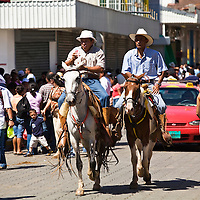 Two Costa Rican Cowboys ride through the streets of Santa Cruz during the annual carnival