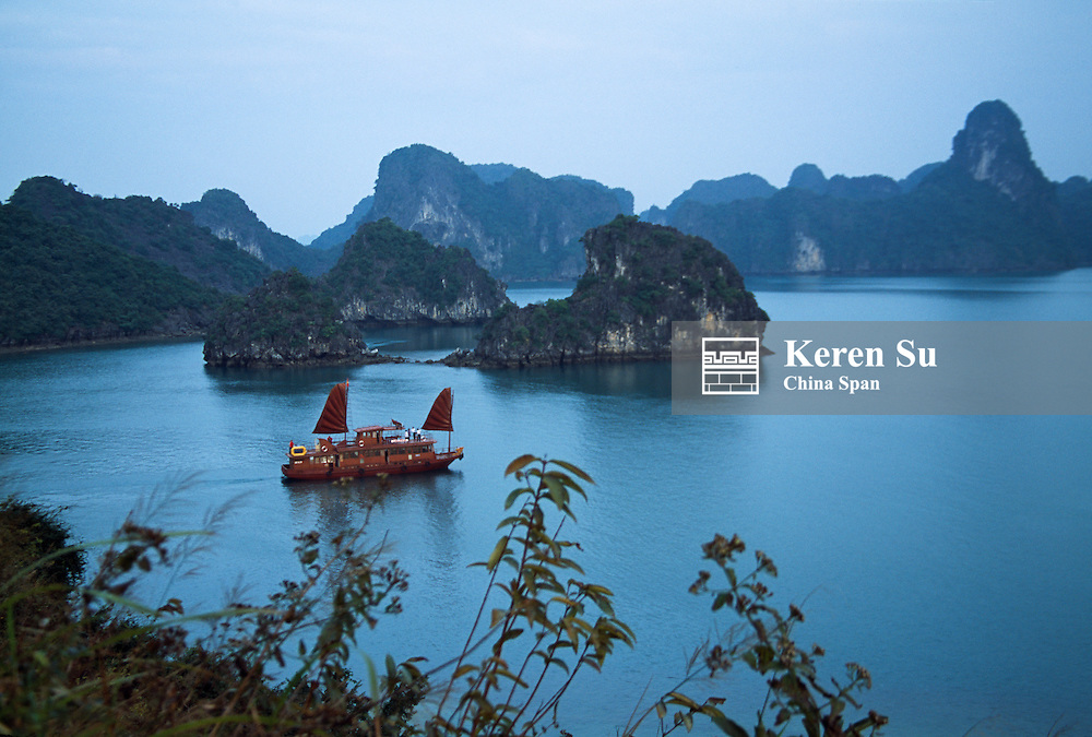 Landscape of limestone karst hills with junk boat sailing in Ha Long Bay, Vietnam