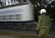 Eine Castorbehälter fährt auf einem Spezialtieflader an einem Polizisten vorbei...A Castor transport passes a police officer. Protests against the 8. transport of castor containers to gorleben, germany. The rural region is legendary for it´s populations non-violent movement againts nuclear power since the mid 1970s.