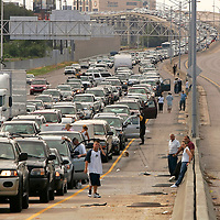 This picture story: Hurricane Katrina - Before, During and After....This picture: Drivers and passengers wait outside their vehicles as traffic snarls on the interstate highway leaving downtown New Orleans August 28, 2005. Authorities in New Orleans ordered hundreds of thousands of residents to flee on Sunday as Hurricane Katrina strengthened into a rare top-ranked storm and barreled towards the vulnerable U.S. Gulf Coast city.