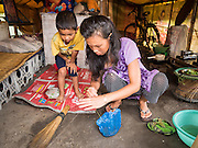 05 AUGUST 2015 - KATHMANDU, NEPAL: A boy helps his mother clean their tent in a large Internal Displaced Person (IDP) Camp in the center of Kathmandu. The camp is next to one the most expensive international hotels in Kathmandu. More than 7,100 people displaced by the Nepal earthquake in April live in 1,800 tents spread across the space of three football fields. There is no electricity in the camp. International NGOs provide water and dug latrines on the edge of the camp but the domestic waste water, from people doing laundry or dishes, runs between the tents. Most of the ground in the camp is muddy from the running water and frequent rain. Most of the camp's residents come from the mountains in northern Nepal, 8 - 12 hours from Kathmandu. The residents don't get rations or food assistance so every day many of them walk the streets of Kathmandu looking for day work.    PHOTO BY JACK KURTZ
